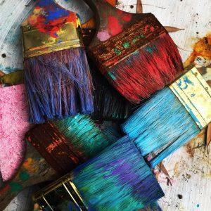 Pinceaux colorés plein de peintures rouge et bleue