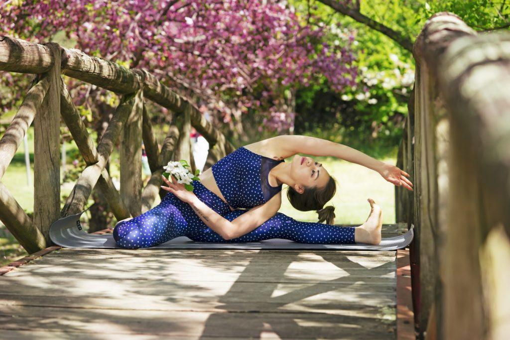 Jeune femme qui fait une séance de yoga dans son jardin feng shui