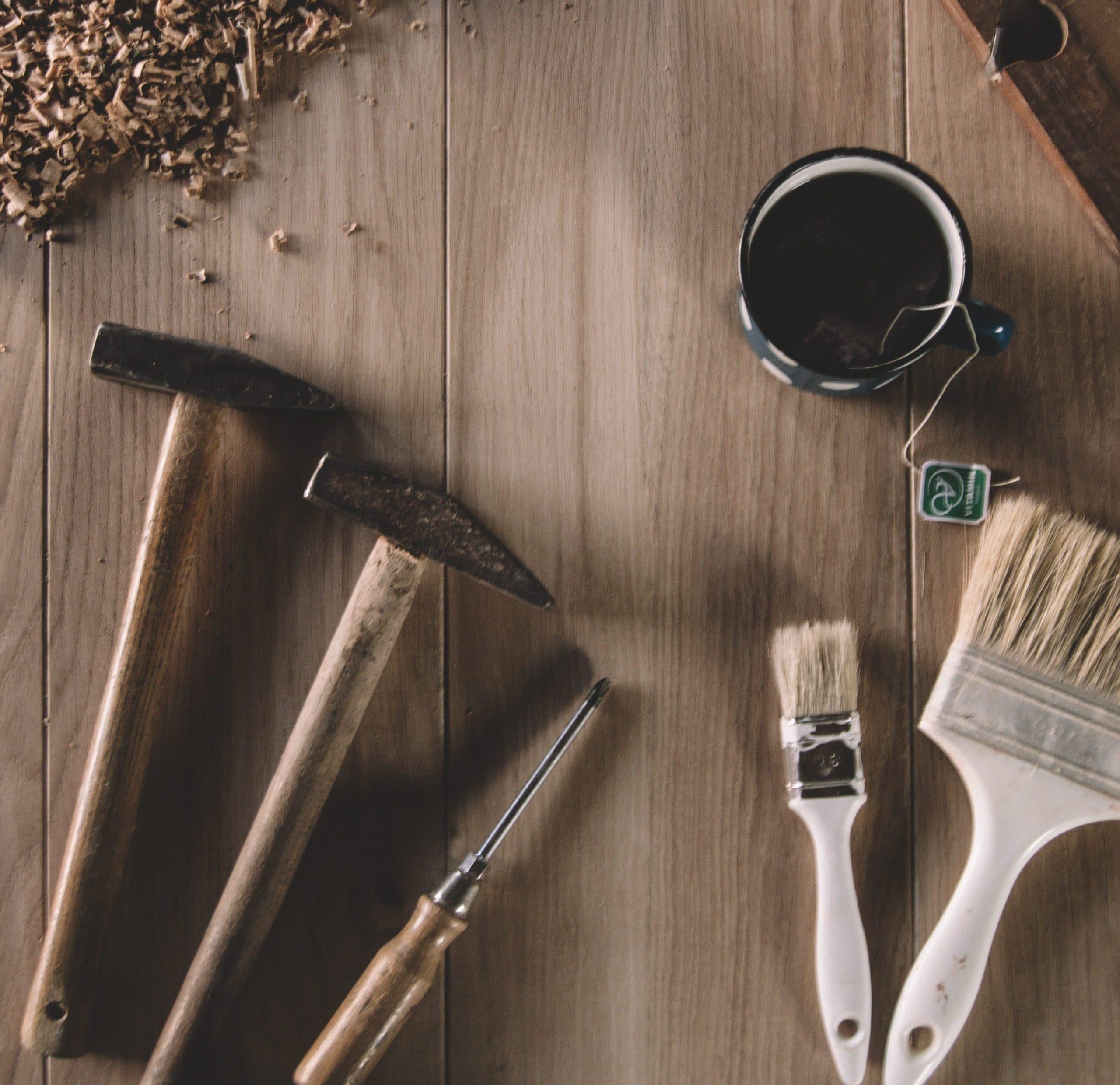 Marteaux et pinceaux posés sur une planche en bois pour faire du bricolage