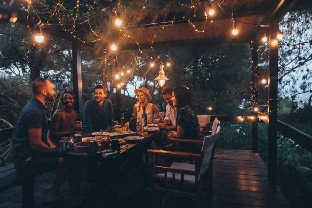 Table d'amis sur une terrasse la nuit l'été