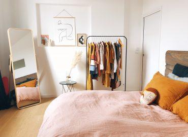 Chambre avec un portant de vêtements, un grand miroir et des cadres décoratifs