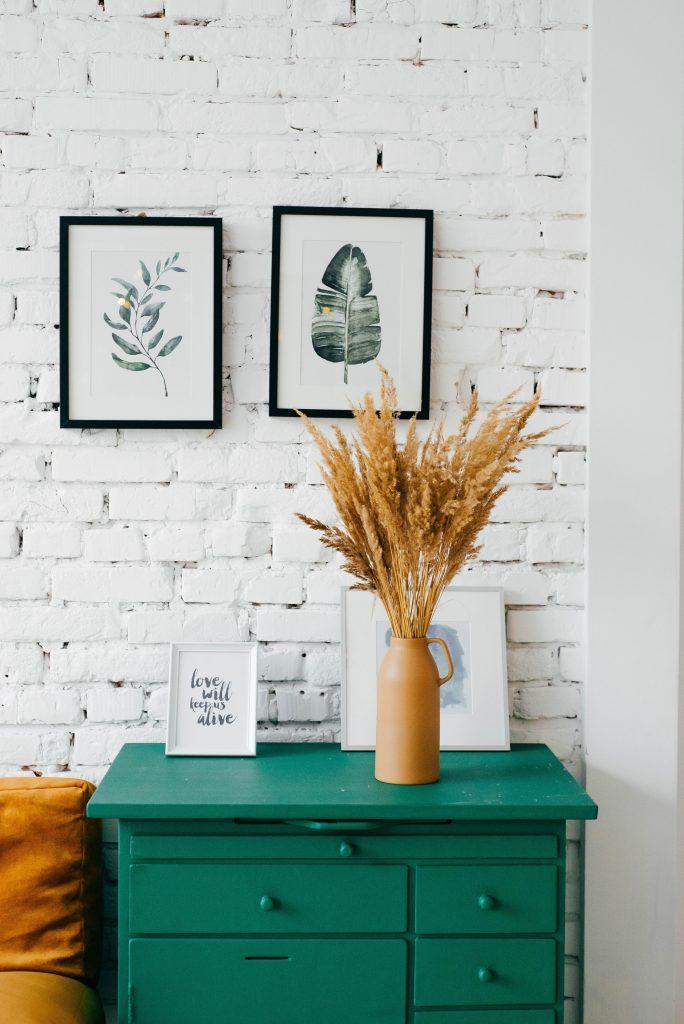 Une commode verte devant un mur de brique et des tableaux